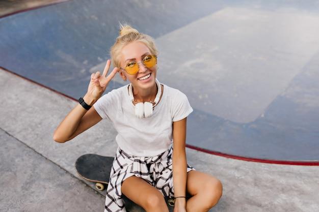 Donna graziosa pattinatrice con acconciatura alla moda in posa con il segno di pace. signora abbronzata alla moda in cuffie che si siede sullo skateboard.