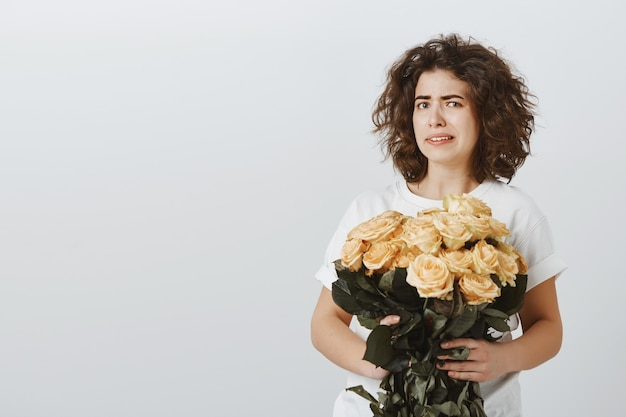 Pretty skeptical girl cringe as looking at flowers, don't like roses, being unimpressed