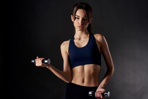 手にダンベルを持つかなり細い女性は、フィットネストレーニングを行使します。高品質の写真