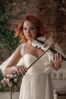 바이올린과 날개를 가진 예쁘고 날씬한 여자 프리미엄 사진