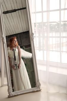 Симпатичная стройная женщина со скрипкой и крыльями