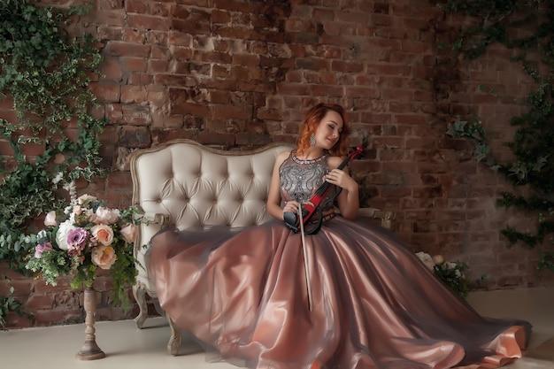Довольно стройная женщина со скрипкой на старом диване