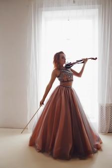 Довольно стройная молодая женщина со скрипкой у окна