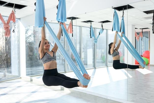 Девушка фитнеса довольно стройного тела делает упражнения летать йогой в тренажерном зале. спорт для здоровья