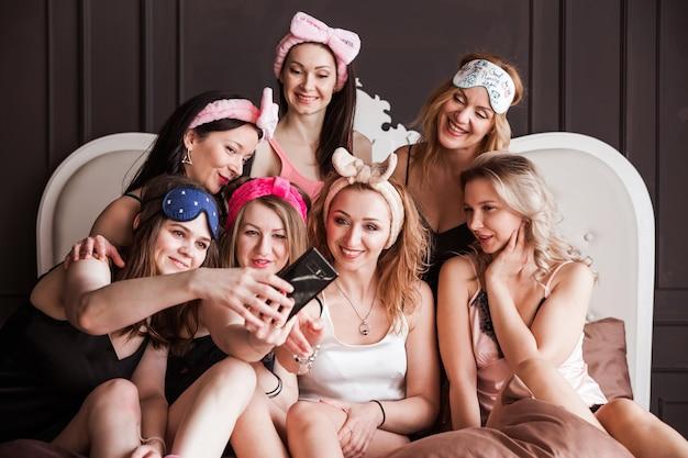 Симпатичные, стройные, очаровательные, стильные, привлекательные, жизнерадостные девушки в пижамах наслаждаются встречей в помещении, отмечают праздник, мероприятие, день рождения, снимая автопортрет на фронтальную камеру, используя смартфон