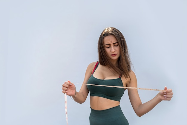 Pretty slim girl in green sportwear measures her waist with a centimeter tape. health and diet concept