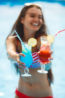 Pretty slim girl offering cocktails. cheerful woman in the swimming pool.