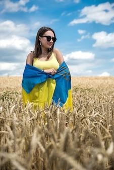 小麦畑でウクライナの黄青の旗を持つかなりスリムな女の子。ライフスタイル