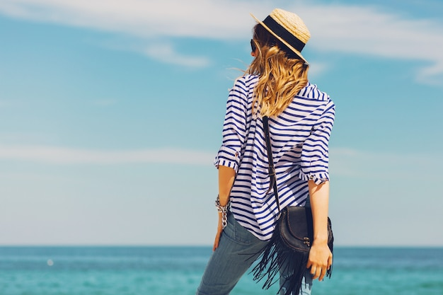 Довольно стройная загорелая стильная блондинка в соломенной шляпе и солнцезащитных очках позирует на райском тропическом пляже