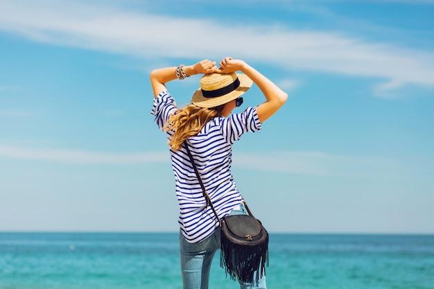 麦わら帽子とサングラス、パラダイスの熱帯のビーチでポーズでかなりスリムな日焼け金髪のスタイリッシュな女性