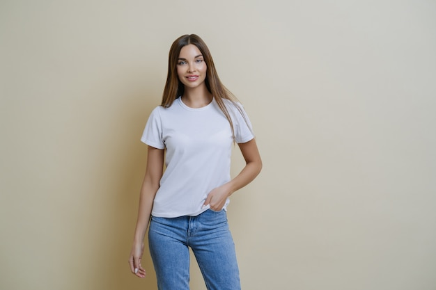 Pretty slim woman keeps hand in pocket, wears casual t shirt and jeans, stands in relaxed pose, self confidence.