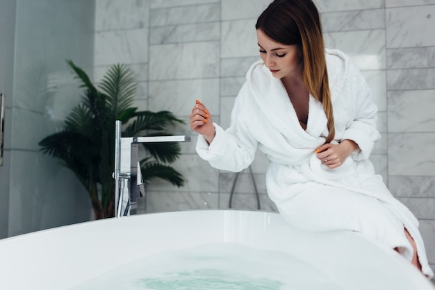 물을 채우는 욕조 가장자리에 앉아 목욕 가운을 입고 꽤 날씬한 여자.