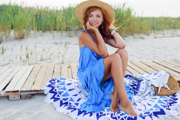 Довольно стройная женщина с длинными рыжими волосами в соломенной шляпе проводит удивительный отпуск на пляже. в синем платье. сидя на стильной обложке.