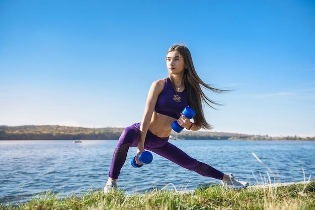 湖の健康と美容の概念の近くでダンベルを扱うかなりスリムな女性