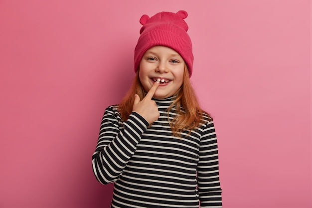 Pretty small ginger girl shows her first adult two teeth, laughs and rejoices, expresses positive emotions, keeps mouth opened, prepares for oral checkup, dressed in striped sweater and pink hat