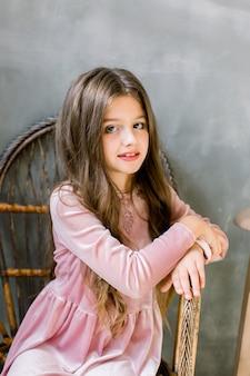 美しいピンクのドレスでかなり小さな女の子が木製の椅子に座っているし、夢のような、美しさとファッションのコンセプト、屋内ポートレート Premium写真