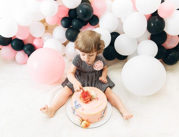 風船とケーキを持つかわいい女の子。スタイリッシュなファッションルック。誕生日のコンセプト。