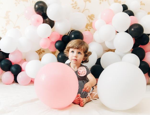 Ballons와 함께 아주 작은 소녀. 세련된 패션 봐.