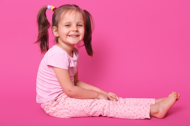 Pretty small kid with two pony tails and many colourful scrunchies sits on floor and glad to be photographed in photo studio. adorable child smiles. children and childhood concept.