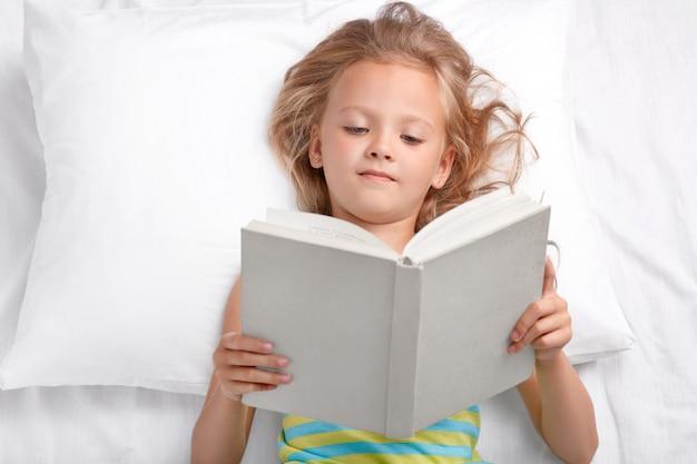 Pretty small preschooler reads attentively interesting story