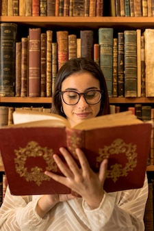Pretty smart woman reading book near shelf