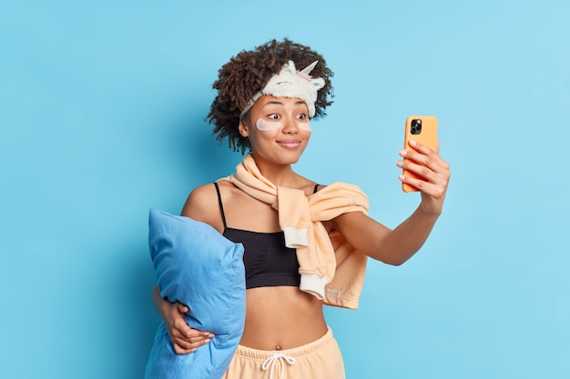 잠옷 수면 마스크에 예쁜 웃는 아프리카 계 미국인 여성이 베개를 보유하고 휴대 전화를 통해 셀카가 콜라겐 패치를 적용합니다.
