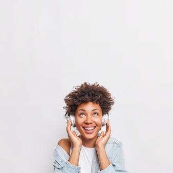 Pretty smiling african american woman listens music via headphones