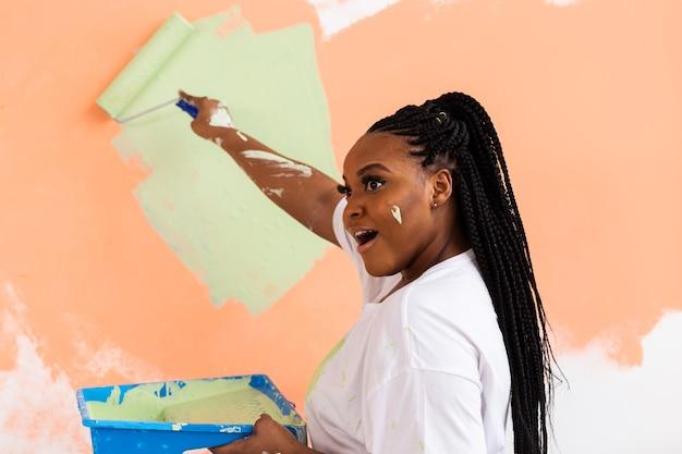 Довольно улыбается афро-американских женщина живопись внутреннюю стену дома с малярным валиком. косметический ремонт