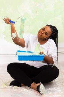 Довольно улыбается афро-американских женщина живопись внутреннюю стену дома с малярным валиком.