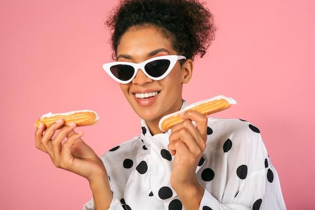 Довольно улыбается африканская женщина держит сладости и позирует на розовом фоне