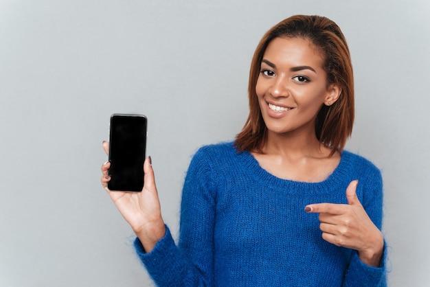 파란색 스웨터를 입은 꽤 웃고 있는 아프리카 여성이 빈 스마트폰 화면을 보여주고 전화에 그녀의 손가락을 보여줍니다. 격리 된 회색 배경