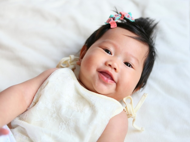 Pretty smiling asian baby girl lying in the bed