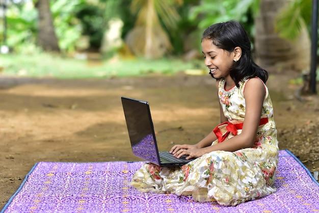 じゅうたんの上に座っている黒いノートとかわいい、笑顔のアジアの女の子