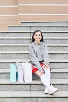 ショッピングバッグの隣の階段に座っているかなり笑顔のアジアの10代の少女