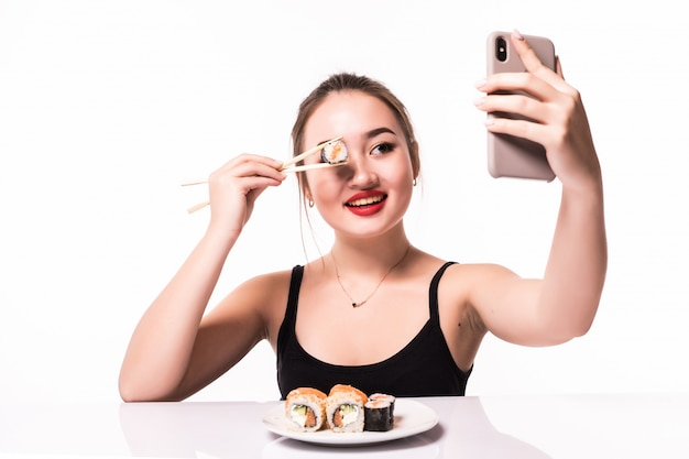 Pretty smiling asian woman cover her eye with sushi roll and make selfie on her phone