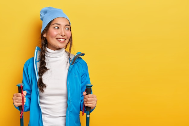 Pretty smiling asian woman enjoys scandinavian walking, has hiking trip, looks aside,  has combed plait, wears blue hat and jacket, holds trekking poles, isolated on yellow wall