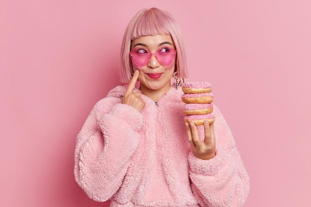 유행 분홍색 머리를 가진 꽤 웃는 아시아 여자 연인 선글라스를 착용하고 모피 코트는 도넛 더미를 보유하고 뭔가에 대한 실내 꿈을 포즈. 흑백 촬영. 여성 도넛을 먹고 즐긴다