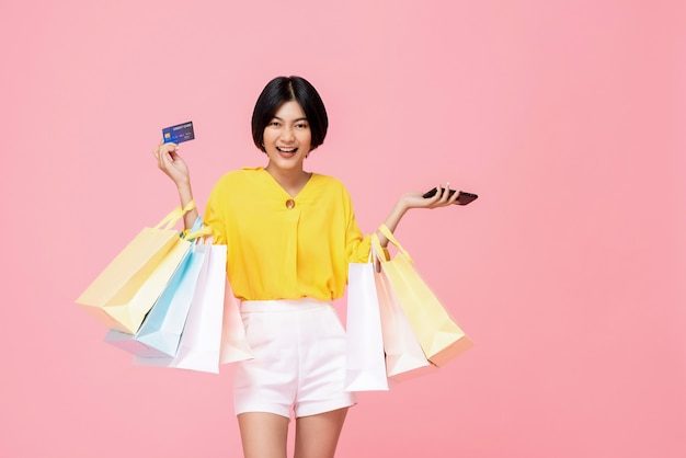 Pretty smiling asian woman with shopping bags showing credit card