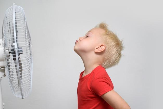빨간 셔츠와 시원한 공기를 즐기는 닫힌 된 눈에 꽤 웃는 금발 소년. 여름 컨셉