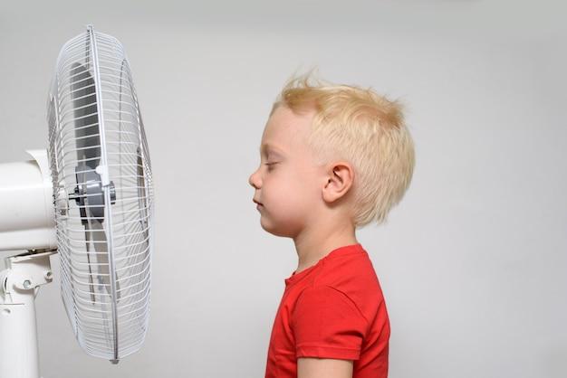 Довольно улыбающийся белокурый мальчик в красной рубашке с закрытыми глазами, наслаждаясь прохладным воздухом. летняя концепция