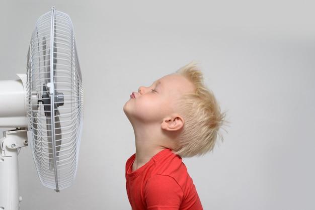 Довольно улыбается белокурый мальчик в красной рубашке и закрытыми глазами, наслаждаясь прохладным воздухом. летняя концепция