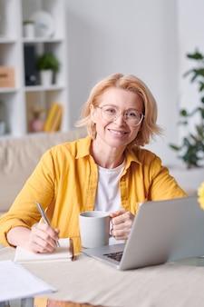 自己隔離中に自宅で仕事をしながらあなたを見ているカジュアルウェアと眼鏡でかなり笑顔の金髪の実業家