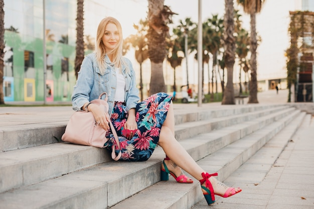 Pretty smiling blond woman sitting on stairs in city street in stylish printed skirt and denim oversize jacket with leather backpack