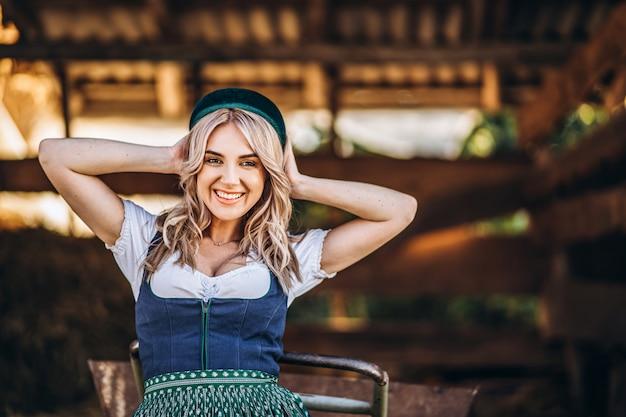 裏庭で働く手押し車で伝統的な衣装でかなり笑顔のブロンド。