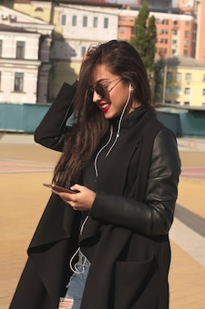 Довольно улыбается брюнетка женщина слушает музыку по мобильному телефону, гуляя по улице