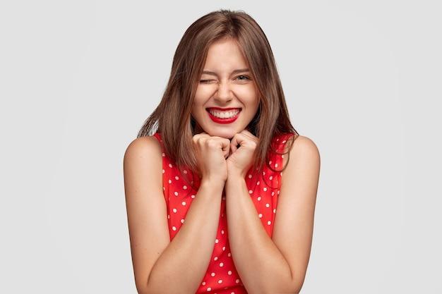 Довольно улыбается брюнетка молодая женщина позирует у белой стены