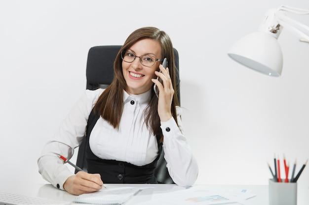 机に座って、明るいオフィスでドキュメントと現代のコンピューターで働いて、携帯電話で話し、楽しい会話を行うスーツを着たかなり笑顔のビジネス女性
