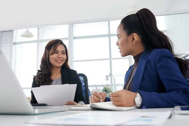 Pretty smiling businesswoman discussing business ideas with colleague and taking notes in planner