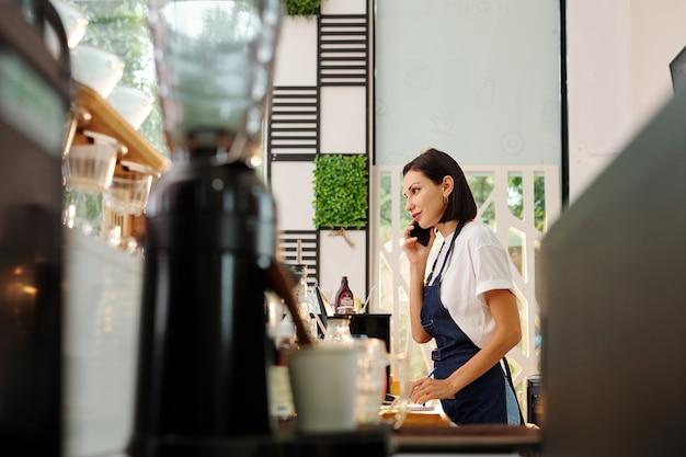 Довольно улыбающаяся официантка кафе стоит у стойки, разговаривает по телефону с клиентом и делает заметки