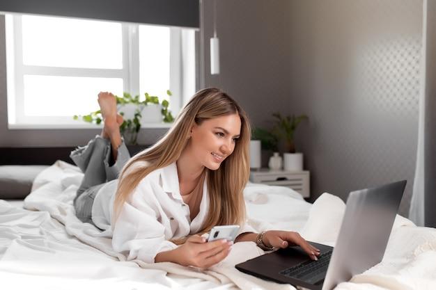 Довольно улыбается кавказская девушка лежит на кровати в спальне и использовать ноутбук для удаленной работы.